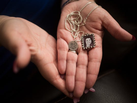 Tracey Williams holds a necklace that carries a picture