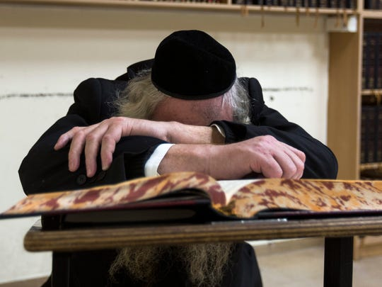 An elderly Jew is in deep prayer in the main hall of the Jerusalem synagogue where three American rabbis were killed.