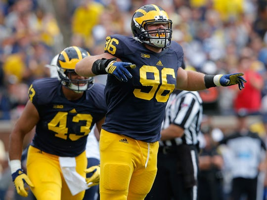 Ryan Glasgow #96 of the Michigan Wolverines celebrates after tackling Adam Hine of the Brigham Young Cougars for a loss at Michigan Stadium on September 26, 2015 in Ann Arbor, Michigan.