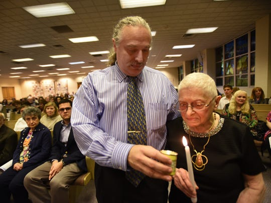 Holocaust survivor Agnes (Bracha) Adler (age 86), of Westwood, and her son Daniel Adler light a candle during the Holocaust Remembrance Day at Temple Emanuel of the Pascack Valley in Woodcliff Lake, photographed on April 23rd, 2017.