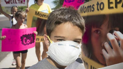 Keegan Cheshire , 7, protests at Salt River Project's headquarters Friday urging environmental regulators to force additional pollution controls on the company'??s coal-fired power plant near Page.