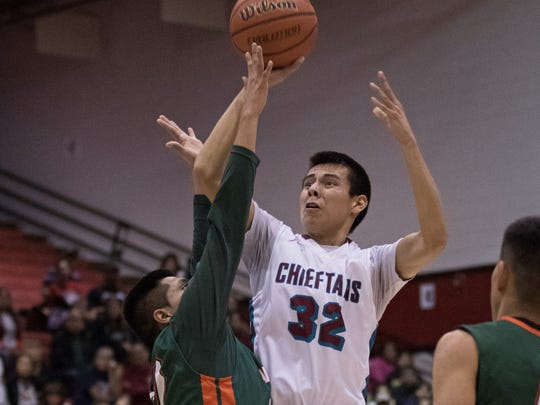 Shiprock's Guy Naseyowma shoots a one-handed jumper over Wingate's Manuelito Chee on Thursday at the Chieftain Pit in Shiprock.