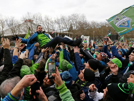 Seattle Sounders forward Herculez Gomez crowd-surfs during a celebration rally Tuesday at the Seattle Center,.