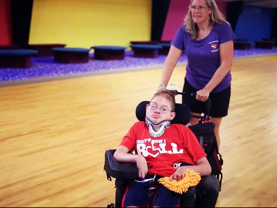 Daniel Johnson, 18, who has been diagnosed with cranium bifidum, is pushed in a wheelchair by his mother, Michelle Johnson, at Skateland USA for Aubrey Binnarr's fourth birthday on Tuesday, August 30, 2016 in Clemson.