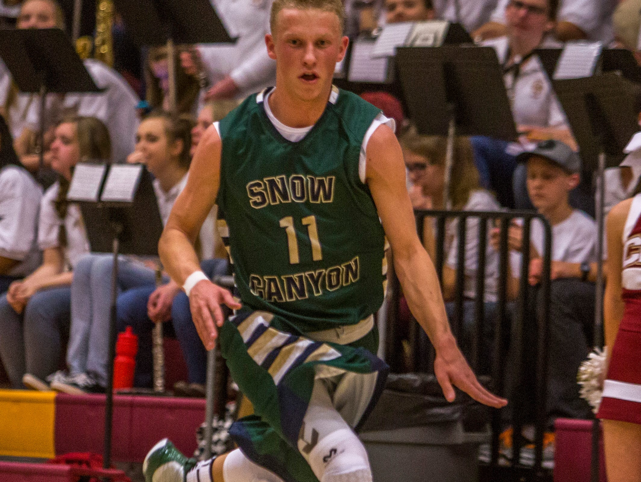 Snow Canyon's Caeden Barney (#11) dribbles the ball up the floor during the game against Cedar, Wednesday, Jan. 13, 2016.