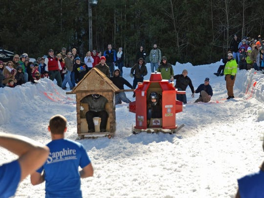 Teams race in custom outhouses, complete with a toilet seat and toilet paper roll, in the annual Great Outhouse Race.
