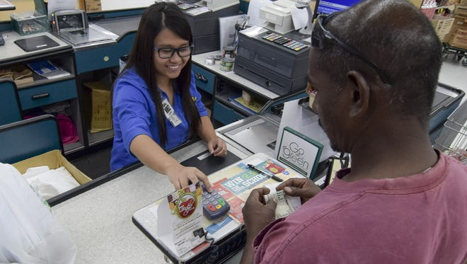 In this September 2015 file photo, Nhez Espinosa checks out a customer at the Pay-Less Supermarket in Mangilao. Guam residents are eligible for the federal Supplemental Nutrition Assistance Program, which gives them food assistance via electronic transfer each month. The Commonwealth of the Northern Mariana Islands is trying to convince the federal government that CNMI residents should be eligible for SNAP as well.