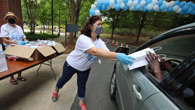 Karen Menting hands out masks as the city of Gastonia and Parkdale Mills gave away 5,000 free masks Saturday during the 'I Wear, I Care' event held on Cotton Blossom Circle Saturday morning, Aug. 1, 2020.