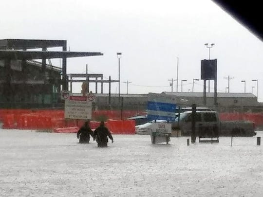 Two men wade through waist-high rain water on Sunday with the new port of entry construction site in the background.