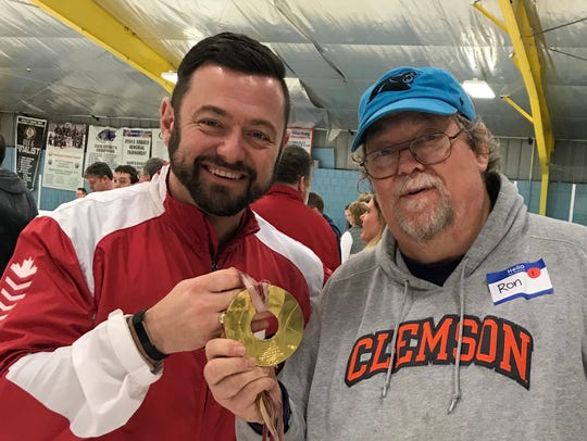 Olympic gold medalist Jamie Korab, left, with columnist Ron Barnett, and the medal Korab won in 2006.