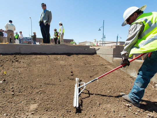 Garrett Western Construction worker Eliazar Mendoza, right, works at the downtown civic plaza on Monday, April 25, 2016, while Mayor Ken Miyagishima looks out at the view from the stage during a tour with other city officials,