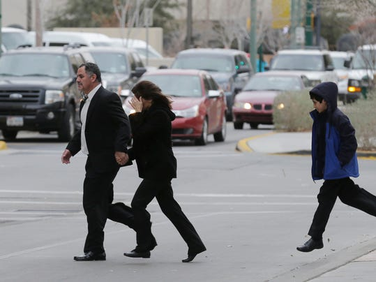 Former EPISD administrator Myrna Gamboa runs across the street hiding her face, with her husband and son, from the federal courthouse after her sentencing. Gamboa was sentenced to five years of probation for her part in the EPISD cheating scandel.