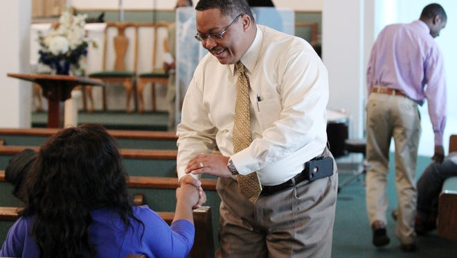 Rev. Greg Randell, pastor of Solid Rock Missionary Baptist Church and a Lafayette Police officer, greets congregants before church service Sunday, January 25, 2015, in Lafayette, La.