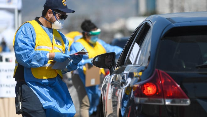 San Bernardino County public health workers in March 2020 conduct drive-thru coronavirus testing in San Bernardino.
