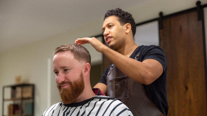 Juan Abreu, owner of the El Cid Barbershop, cuts the hair of Chris Flynn. Abreu said he wanted to close up shop because of the coronavirus but remained opened. (Provided by El Cid Barbershop).
