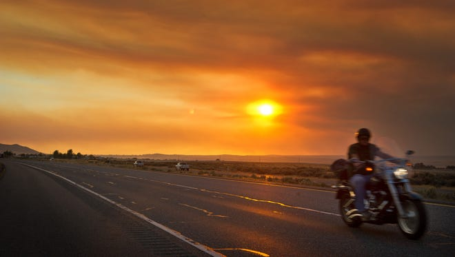 Traffic rolls east along Hwy 82 with a backdrop of brown smoke from a fire just outside Prosser, Wash., that grew to an estimated 1,000 acres and was threatening homes.