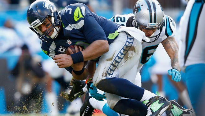 Seattle Seahawks quarterback is tackled by Cortland Finnegan during the NFC Divisional Playoff Game at Bank of America Stadium last Sunday in Charlotte,