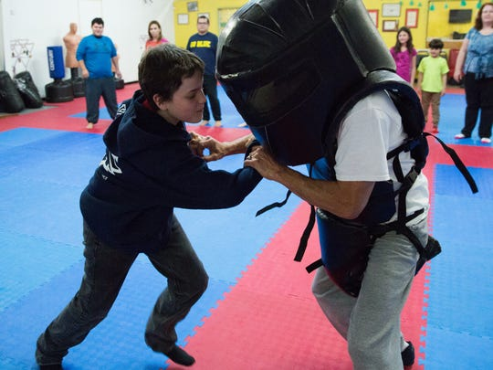 Zack Lackey, 13, practices self-defense techniques on Tom Baca one of the instructors at Gold Medal Taekwondo. Assaults and rape can happen to men, women and children, which is why an inclusive class is offered.
