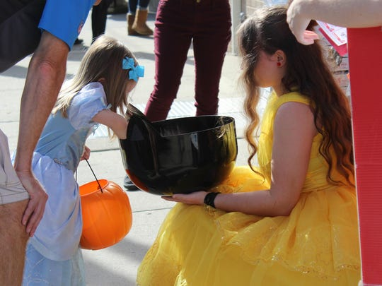 Addison Harmon, 3, dressed as Cinderella, chooses her candy from a bowl held by Emily Granda, dressed as Belle.