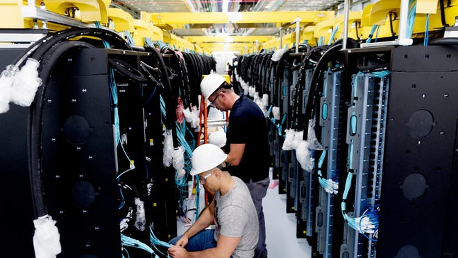 Workers install the fiber-optic cable within the cabinets during the installation of the Summit supercomputer at Oak Ridge National Laboratory on Sept. 12, 2017. Summit is composed of hundreds of cabinets of servers and miles of fiber-optic cable.