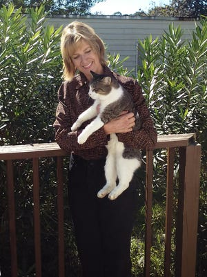 Kathi Culbreth holds Ceasar, an indoor cat that was recently abandoned by its owners.