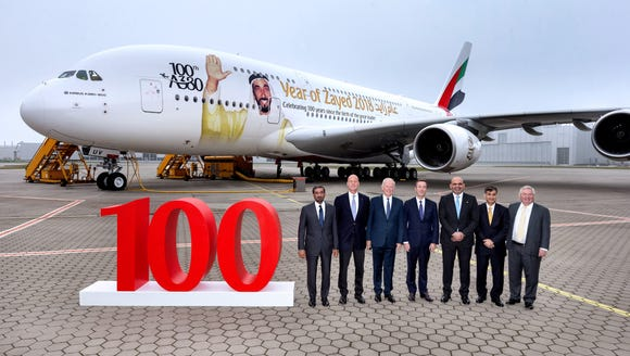 Emirates and Airbus officials pose with Emirates airline's