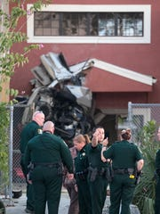Lee County Sheriff's deputies examine a car that crashed into Evangelical Christian School at a high rate of speed on Wednesday, January 17, 2018, in Fort Myers. The driver of the car died.