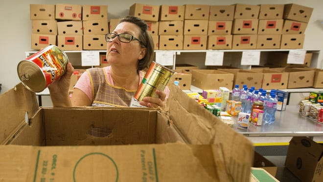 Kathy McMillan, a volunteer checks for dates on donated food at the Harry Chapin Food Bank on Thursday.  The food bank is preparing for the The Letter Carriers' #StampOutHunger Food Drive. This is the biggest one-day drive in the nation. Last year, Lee Co. residents donated 400K pounds of food.