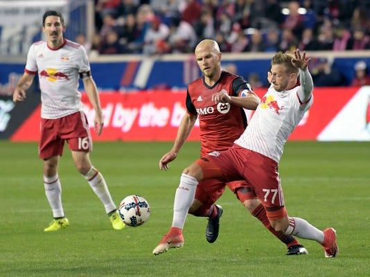 New York Red Bulls midfielder Daniel Royer (77) controls the ball as Toronto FC midfielder Michael Bradley (4) defends during the first half of an MLS Eastern Conference semifinal soccer match Monday, Oct. 30, 2017, in Harrison, N.J. Looking on is Red Bulls midfielder Sacha Kljestan (16). (AP Photo/Bill Kostroun)