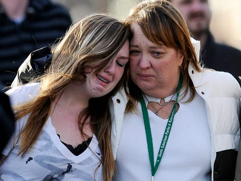 A parent escorts her daughter from Shepherd of the Hills Church after a school shooting at Arapahoe High School on Dec. 13 in Centennial, Colo.