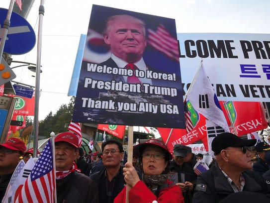 A photo taken on Nov. 8, 2017, shows demonstrators holding a placard showing a picture of President Trump as they wait for his appearance outside the National Cemetery in Seoul. US President Donald Trump's notoriously threatening rhetoric towards nuclear-armed North Korea may have helped bring about a new round of talks between North and South Korea, analysts have said.
