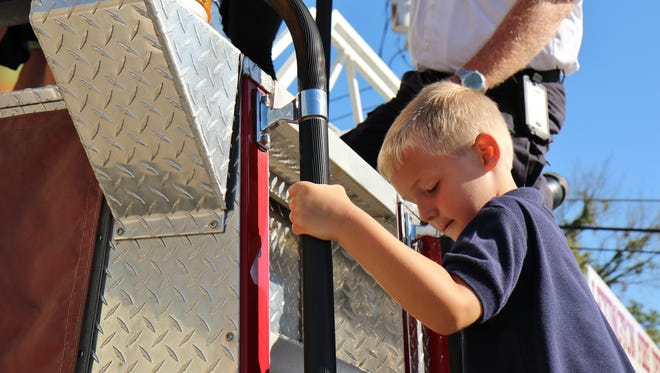 A boy climbs on a fire truck Sunday in Lexington. First United Methodist Church honored first responders, and children were allowed to explore the equipment.
