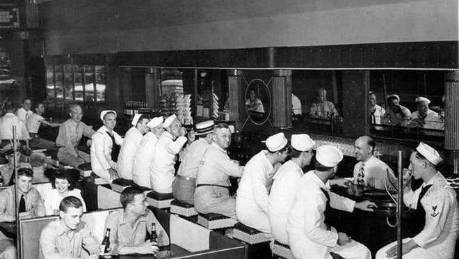 This World War II-era photograph sits behind the bar of The Airliner at 22 S. Clinton St. General Manager Chris Flanders recreated the photo at the bar on Wednesday.