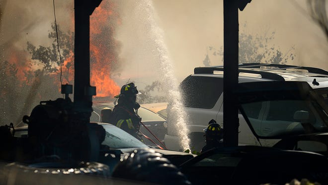 Firefighters from the Green Bay Metro Fire Dept. help battle a fire at Smitty's Auto Salvage yard in Bellevue on Wednesday, Aug. 12, 2015.