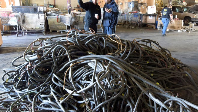 Paz Metals owner Arie Yohanan, left, talks with employee Edwin Batista about a shipment of old powerlines at the Hellam Township business Friday, Nov. 13, 2015. Bill Kalina - bkalina@yorkdispatch.com