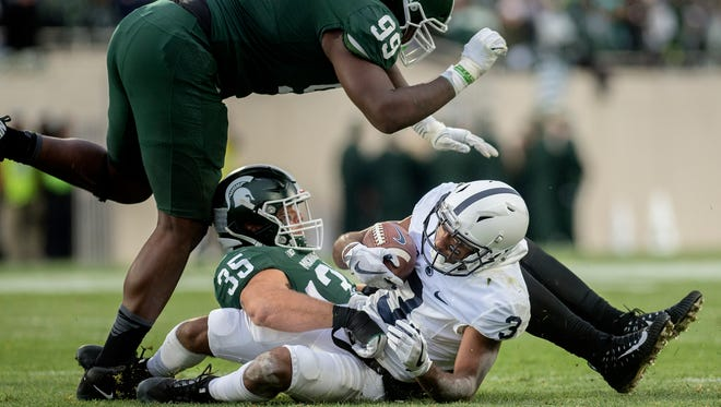 Michigan State's Joe Bachie tackles Penn State's Penn State's DeAndre Tompkins during the second quarter on Saturday, November 4, 2017, at Spartan Stadium in East Lansing. Bachie's teammate Raequan Williams, left, closes in.