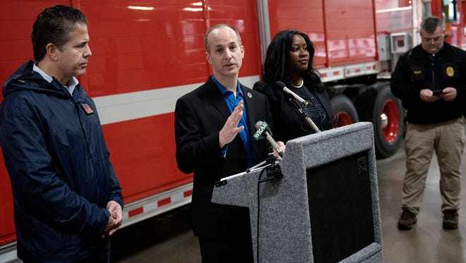Lansing Mayor Andy Schor, center, speaks during a press conference regarding flooding on Friday, Feb. 23, 2018, at the Lansing Fire Department's Station 8. U.S. Rep. Mike Bishop, left, and Lansing Township Supervisor Diontrae Hayes, right, look on.