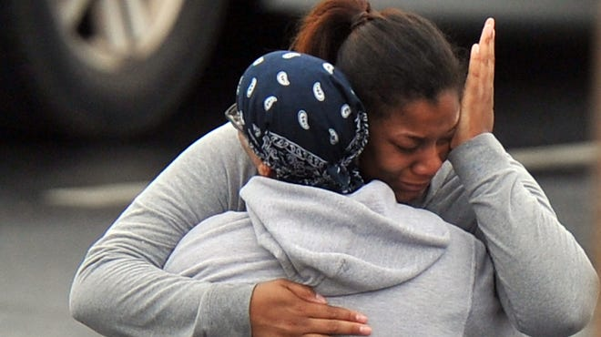 A FedEx employee and a family member embrace after a shooting at a FedEx facility in Kennesaw, Ga., on April 29.