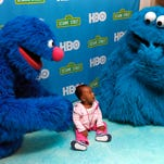 Naomi Johnson, 10, from Avondale, poses with Grover and Cookie Monster during a free museum day hosted by Sesame Street and HBO at the Children's Museum of Phoenix on January 30, 2016.