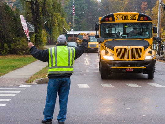 Crossing guard Dick Hough greets school buses leaving
