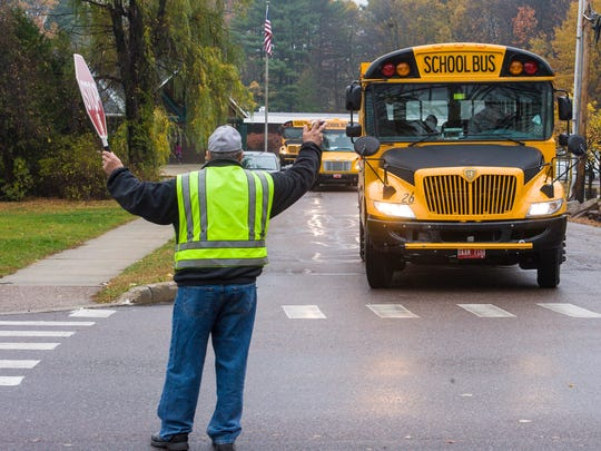 Crossing guard Dick Hough greets school buses leaving