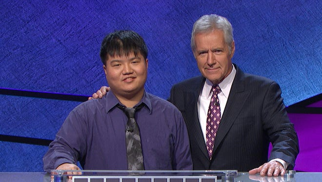 Alex Trebek with contestant Arthur Chu in front of a total of his winnings at a taping of 'Jeopardy!'