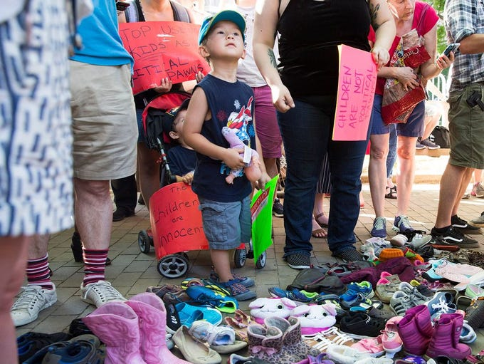 A child stands in front of a pile of children's shoes