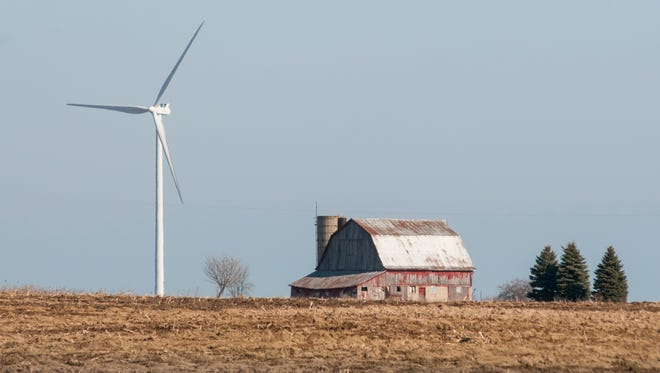 A wind turbine stands in the distance over a barn Monday, Feb. 27, in Deckerville.