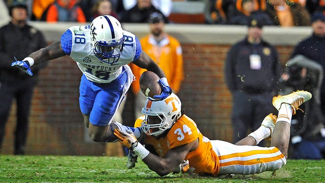 Kentucky running back Stanley Williams (18) is tackled by Tennessee linebacker Jalen Reeves-Maybin (34) on Nov. 15, 2014..