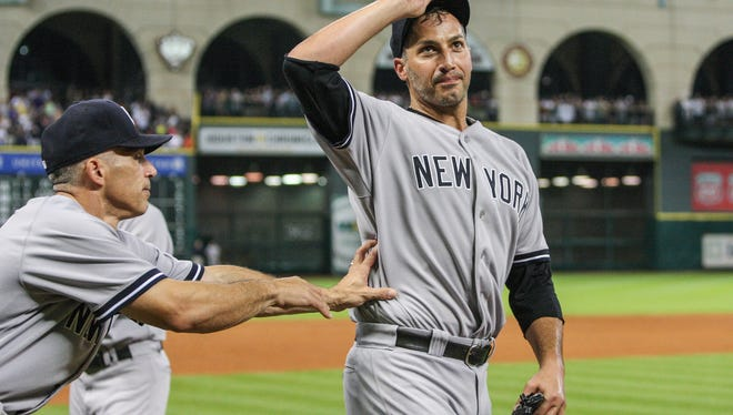 New York Yankees manager Joe Girardi (28) pushes starting pitcher Andy Pettitte (46) back onto the field after defeating the Houston Astros 2-1at Minute Maid Park.