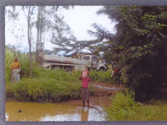 A child retrieves water from a polluted water hole