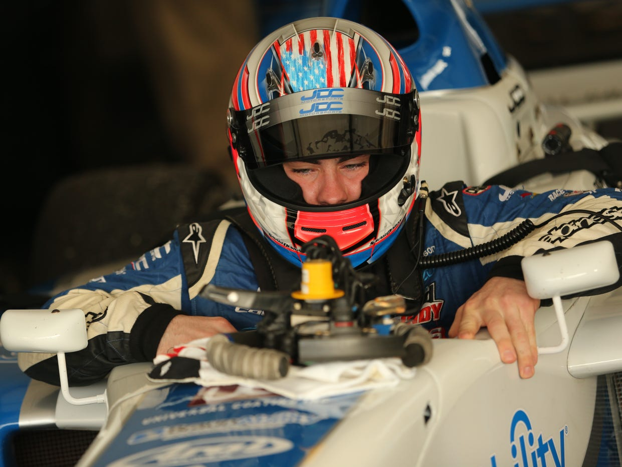 Michael Johnson gets into his car before Friday practice for the Pro Mazda Series on the streets of St. Petersburg, Fla.