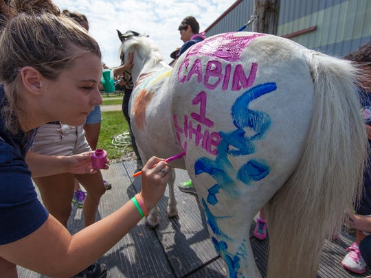 """Counselor Katie Williams puts in a plug for her cabin of kids (there are eight cabins total this year). One of the activities that kept the kids busy all day was painting """"Jack"""" the pony with water paint. After each session, he got a nice cool shower.  There are about 100 counselors and activity staff. All are volunteers."""