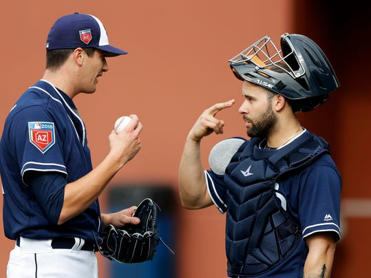 San Diego Padres pitcher Cal Quantrill, left, talks with catcher Raffy Lopez during a baseball spring training workout, Friday, Feb. 16, 2018, in Peoria, Ariz. (AP Photo/Charlie Neibergall)